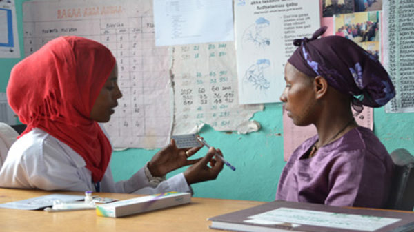 Aminaa and FP client explaining contraceptive pills via Pathfinder International