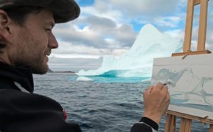 Cory paints an iceberg from the bow of a freighter canoe off the coast of Baffin Island, Nunavut, Canada.