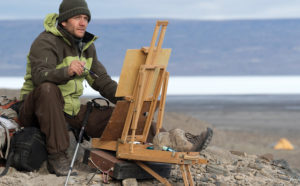 Painting at the top of the world on Ellesmere Island, Nunavut, Canada, with a small tent as a shelter during Cory's month on the island.