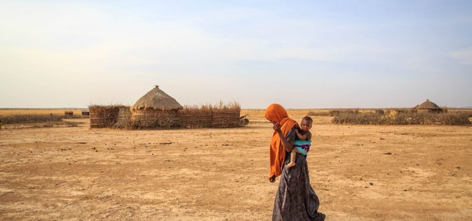 Fartun Hassan, 25, mother of 4, makes her way home in Yahas-Jamal Keble in Somali region of Ethiopia. In the Somali Region, water supply coverage is estimated at 59.7%, lower than the national average of 68.5%. The need for water supply normally increases in the dry season, especially at the time of drought such as in recent years. © UNICEF Ethiopia/2014/Ose