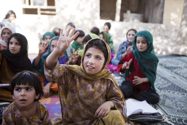Khalida raises her hand to answer a question in the Puti Kalatsha community-based education classPhoto by Elissa Bogos/Save the Children, shared by GSK | Flickr | CC BY 2.0
