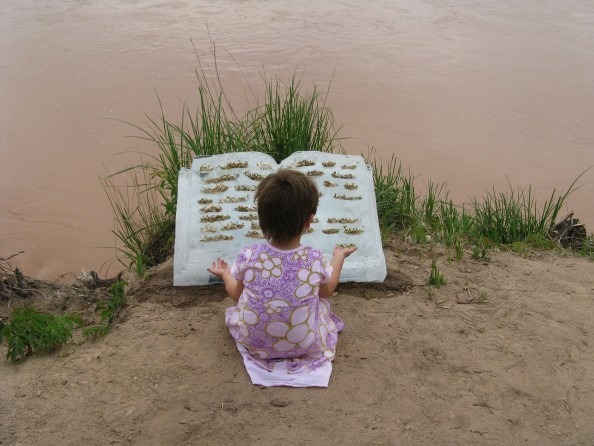 "Engrossed A young girl ""reads"" ice-book text comprised of Fremont cottonwood seed(Populus fremontii) beside the Rio Grande in Albuquerque, New Mexico 