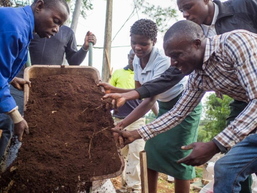 Adding composted cow manure to the soil to bolster nutrients. Left to right: Isaac da Costa, Amg; Juleita Eduardo, student; Beneto Pessero, student; Domingos Reis, Lupa. Photo by Grant Bemis