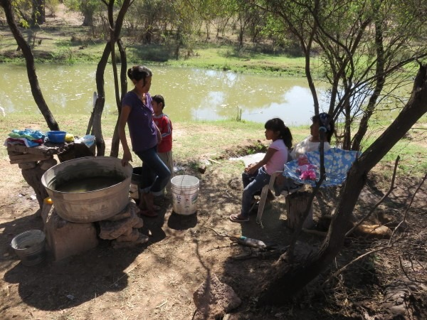 A Yaqui family washes clothes in the pesticide-clogged Río since there is no running water in their village of Tórim. By Basia Irland