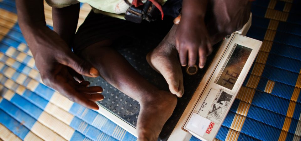 WFP Nutrition Programme, North Darfur A community volunteer weighs a child with malnutrition at a food distribution centre in the Rwanda camp for internally displaced persons (IDPs), near Tawila, North Darfur. More than 8,000 women and children living in the camp benefit from nutrition programmes run by the World Food Programme (WFP).Photo by United Nations Photo   Flickr    CC BY-NC-ND 2.0