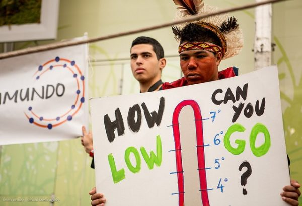 """Youth activists from the Indigenous Peoples' Caucus hold a sign that reads """"How low can you go?"""" 