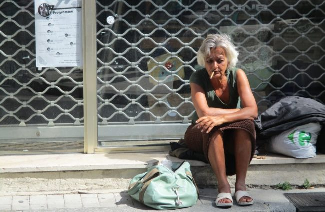 Poor woman with cigarette sitting in front of shop window