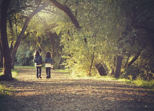 Photo of two young people walking through forest